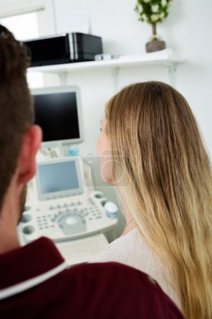 Expectant Couple Looking At Ultrasound Machine