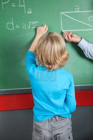 Little Boy Writing Formula On Greenboard