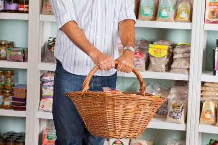 Photo for Midsection on mid adult man holding wicker basket against shelves in grocery store - Royalty Free Image