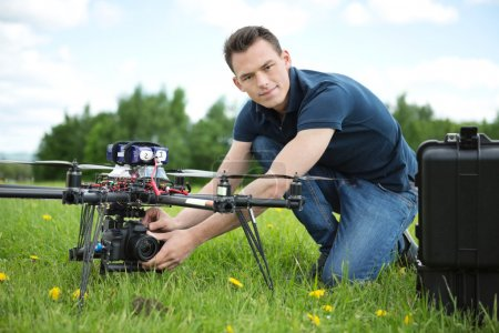Photo for Portrait of confident young engineer setting camera on photography drone in park - Royalty Free Image