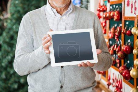 Photo pour Abdomen d'homme senior tenant la tablette numérique dans le magasin de Noël - image libre de droit