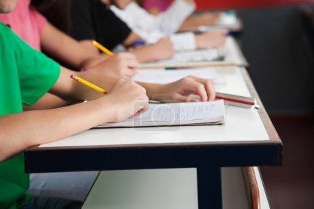 Photo pour Midsection des lycéens écrivant sur papier au bureau en classe - image libre de droit