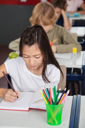Schoolgirl Writing In Book At Classroom