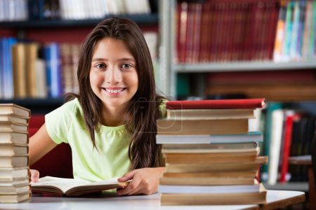 Schoolgirl Smiling While Sitting With Stack Of Books In Library