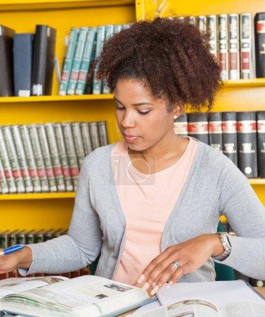 Photo pour Jeune étudiante avec des livres étudiant à table à la bibliothèque du collège - image libre de droit