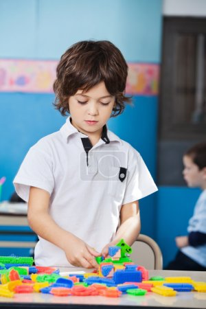 Photo for Little boy playing with colorful construction blocks in classroom - Royalty Free Image