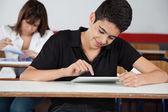 High School Student Using Digital Tablet At Desk
