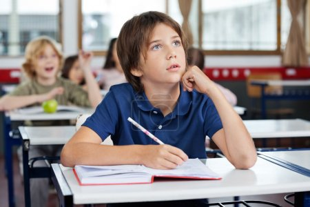 Boy Looking Up While Writing At Desk