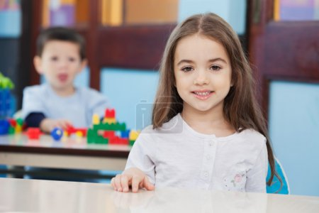 Photo for Portrait of cute little girl with friend in background at preschool - Royalty Free Image