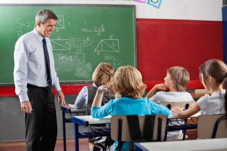 Teacher Looking At Students Sitting In Classroom