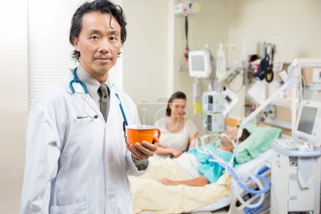 Doctor Holding Coffee Cup With Patient Resting In Hospital