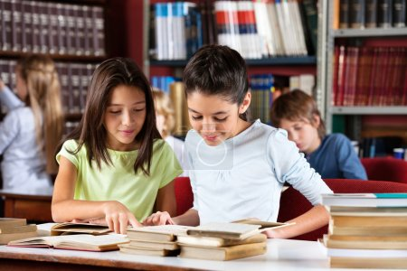 Schoolgirls Reading Book Together At Table In Library
