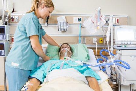 Nurse Adjusting Male Patient's Pillow