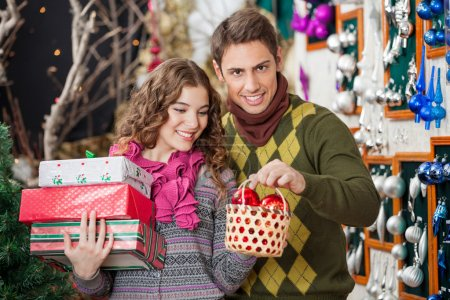 Man With Woman Shopping Presents In Christmas Store