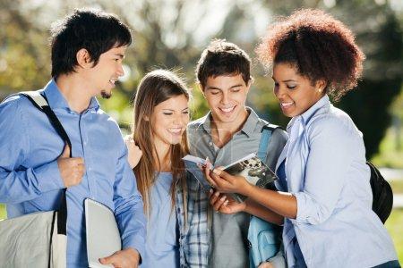 Photo pour Heureux étudiants universitaires lecture livre ensemble sur le campus - image libre de droit