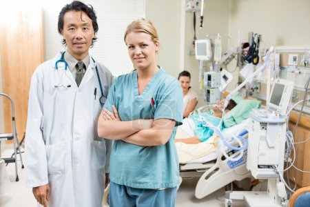 Nurse And Doctor With Patient Resting In Background