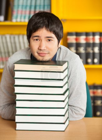 Student Resting Chin On Stacked Books At Table In Library