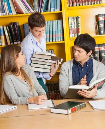 Photo pour Étudiant homme portant des livres tandis que des amis assis à table dans la bibliothèque du collège - image libre de droit
