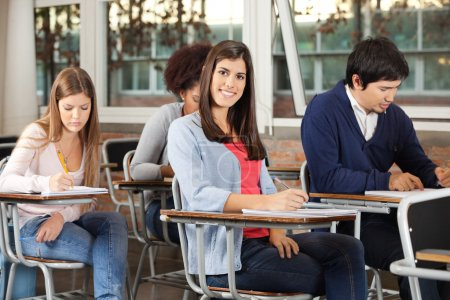 Photo for Portrait of happy young woman with students writing exam in classroom - Royalty Free Image