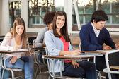 mujer con estudiantes de examen de la escritura en el aula