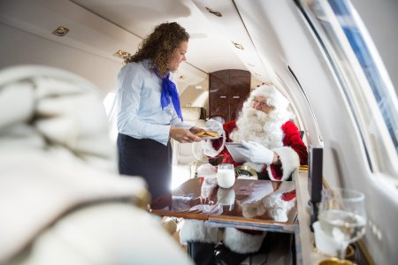 Photo for Mid adult airhostess serving cookies to Santa in private jet - Royalty Free Image