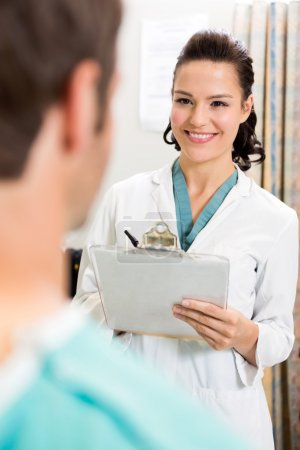 Female Doctor With Clipboard Looking At Patient