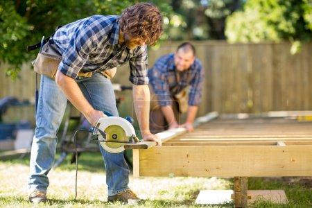 Photo pour Mid adulte menuisier coupe du bois avec scie à main tout en collaborant avec lui en arrière-plan sur le chantier de construction - image libre de droit