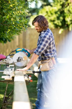 Carpenter Using Table Saw To Cut Wooden Plank At Site