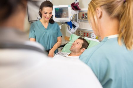 Nurses And Doctor Examining Patient In Hospital