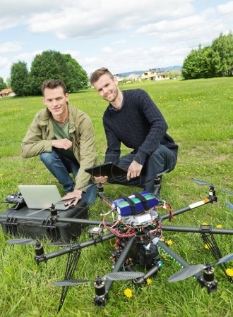 Technicians With Laptop And Digital Tablet By UAV