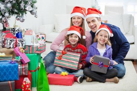 Photo pour Portrait de famille heureuse dans des chapeaux de Père Noël assis par des cadeaux de Noël à la maison - image libre de droit