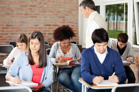 Photo for Group of multiethnic students writing exam while teacher supervising them in classroom - Royalty Free Image