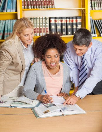 Teachers Assisting Student In College Library