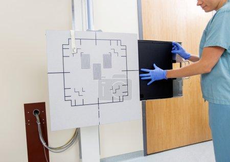 Radiologist Adjusting Xray Film In Machine
