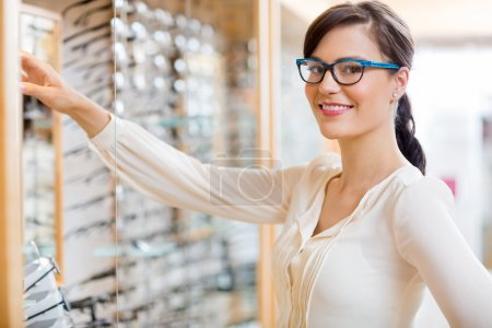 Photo for Portrait of happy young woman buying new glasses at optician store - Royalty Free Image