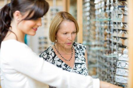 Salesgirl Assisting Woman In Selecting Glasses