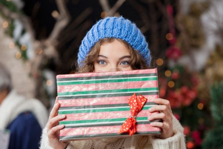 Woman Covering Face With Christmas Present At Store