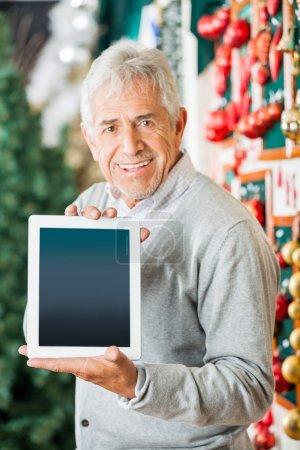 Photo pour Portrait d'un homme senior affichant une tablette numérique tout en se tenant au magasin de Noël - image libre de droit