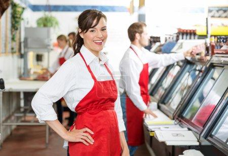 Photo pour Portrait de boucher confiant debout en magasin avec des collègues travaillant en arrière-plan - image libre de droit