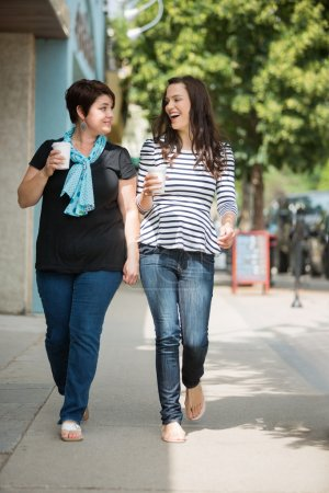 Friends With Disposable Coffee Cups Walking On Pavement