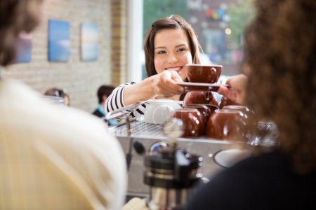 Photo for Young female customer taking coffee from barista in coffee shop - Royalty Free Image