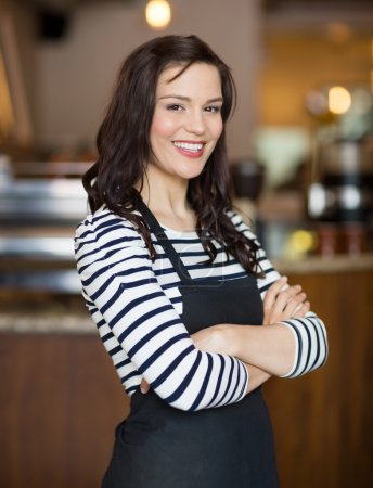 Photo for Portrait of happy young waitress standing arms crossed in cafe - Royalty Free Image