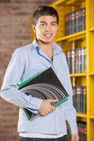 Photo pour Portrait d'un étudiant masculin confiant souriant tout en tenant des livres dans une bibliothèque collégiale - image libre de droit