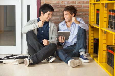 Photo for Happy male students with digital tablet clenching fist while sitting in college library - Royalty Free Image