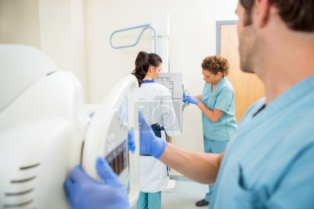 Nurses Adjusting Chest Xray Machines For Patient