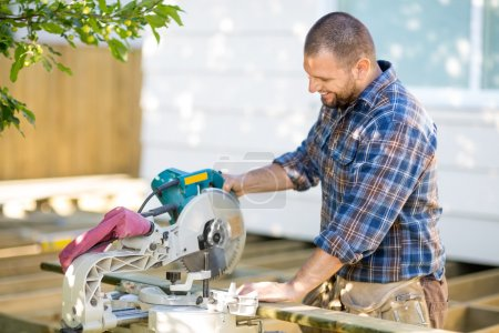 Carpenter Cutting Wood Using Table Saw At Construction Site