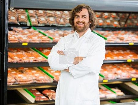 Salesman Standing Arms Crossed In Butcher's Shop