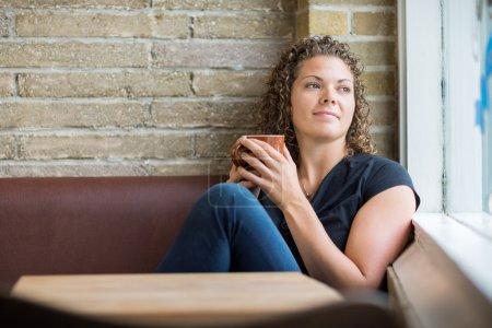 Photo pour Femme réfléchie tenant la tasse de café tout en regardant par la fenêtre dans le café - image libre de droit