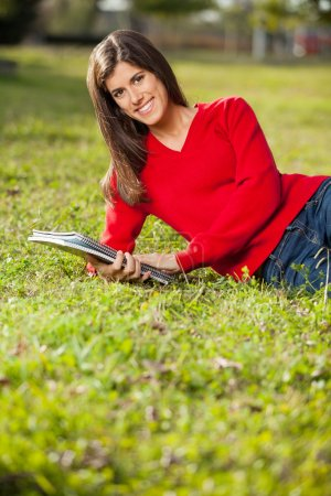 Woman Holding Books While Relaxing On Grass At Campus