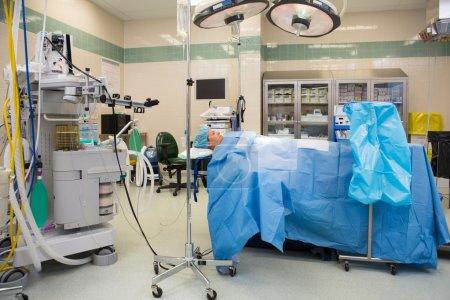 Photo pour Toute la longueur de la patiente couchée sur le lit dans la salle d'opération - image libre de droit